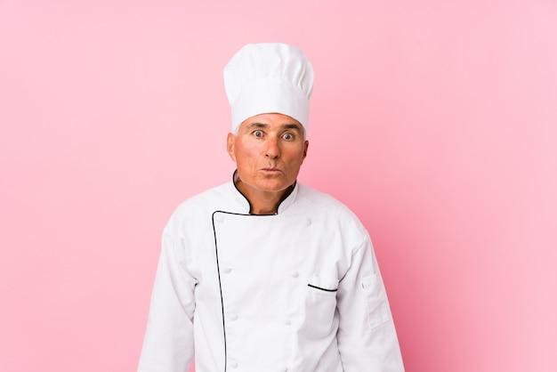 Cozinheiro envelhecido médio encolhe os ombros e abre os olhos confusos.