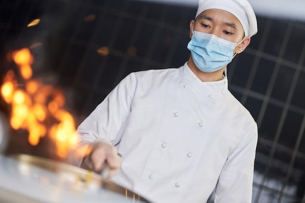 Cozinheiro experiente fazendo refogado com chamas na wok