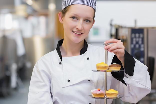 Cozinheiro feliz que prende a bandeja de bolo estratificada