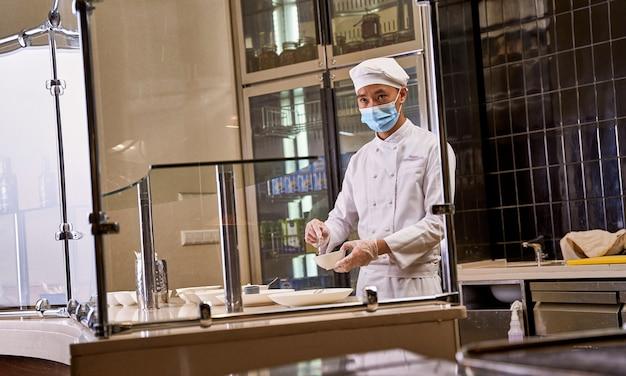 Cozinheiro habilidoso com chapéu de chef e uniforme mexendo uma mistura dentro de uma tigela com uma colher pequena enquanto observa algo no quarto