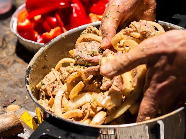 Cozinheiro irreconhecível, misturando pedaços de carne e cebola para shashlik