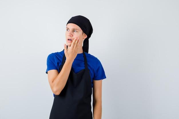 Cozinheiro jovem adolescente com a mão na bochecha, olhando para longe em t-shirt, avental e olhando focado. vista frontal.