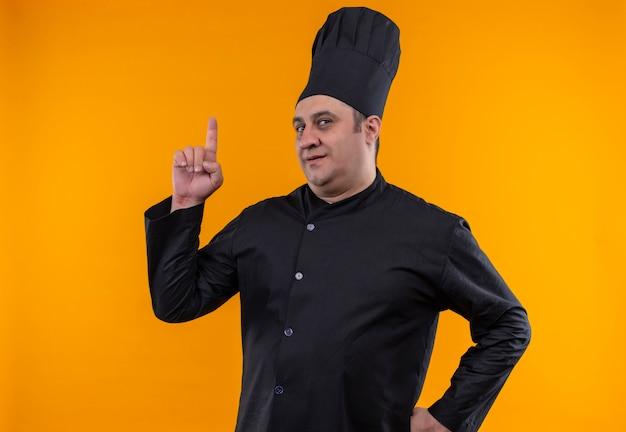 Cozinheiro masculino de meia-idade com uniforme de chef aponta o dedo para cima colocando a mão no quadril na parede amarela com espaço de cópia