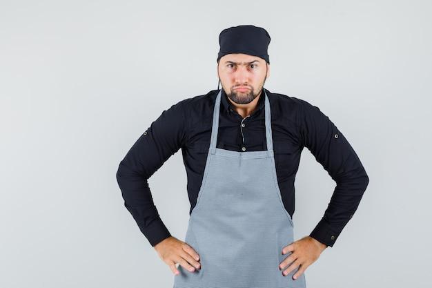 Cozinheiro masculino em pé com as mãos na cintura na camisa, avental e olhando com raiva, vista frontal.