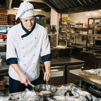 Cozinheiro masculino, fritar a carne na panela no fogão
