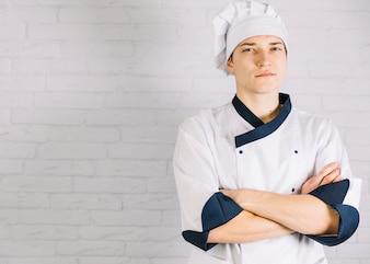 Cozinheiro masculino jovem, cruzando os braços no peito