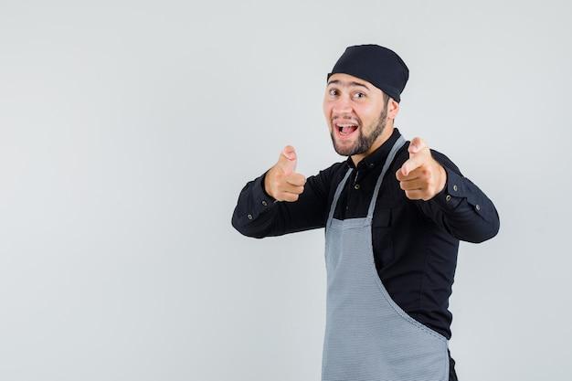 Cozinheiro masculino na camisa, avental, mostrando o gesto da arma apontado para a câmera e olhando feliz, vista frontal.