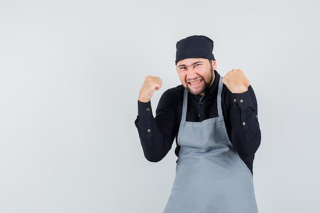 Cozinheiro masculino na camisa, avental, mostrando o gesto do vencedor e parecendo com sorte, vista frontal.