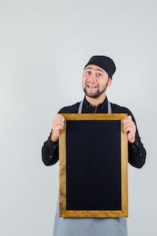 Cozinheiro masculino na camisa, avental segurando o quadro-negro e olhando alegre, vista frontal.