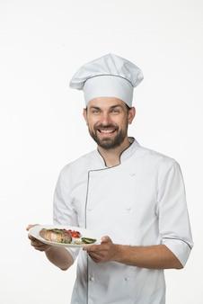 Cozinheiro masculino novo de sorriso no uniforme do cozinheiro chefe que mantém o prato preparado da carne contra o fundo branco