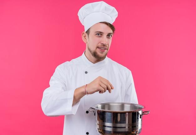 Cozinheiro olhando para o prazer da câmera no rosto e adicionando algo à panela em pé sobre a parede rosa