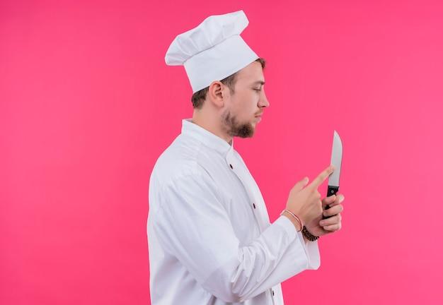 Cozinheiro olhando para uma faca tocando sua posição sobre a parede rosa