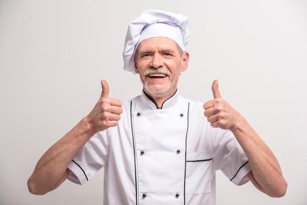 Cozinheiro principal masculino sênior no uniforme que mostra o polegar acima.