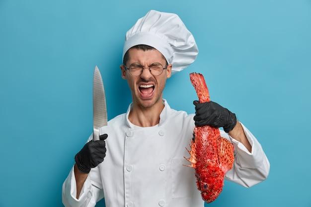 Cozinheiro profissional francês irritado passando muito tempo na cozinha, usa uniforme, luvas de borracha pretas, posa com peixe e faca