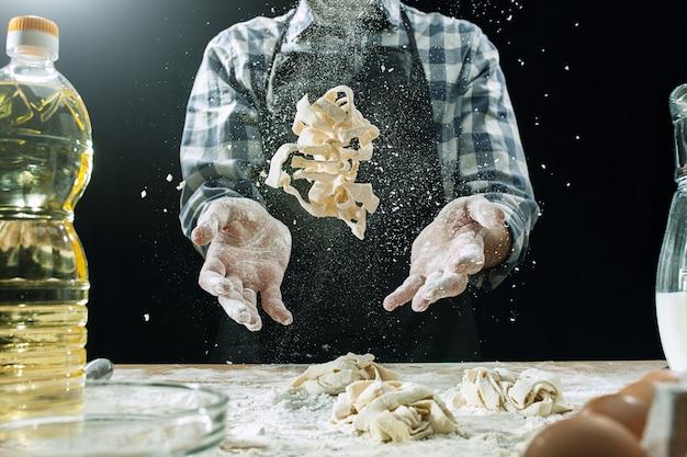 Cozinheiro profissional masculino polvilha a massa com farinha, pré-aparas ou coze pão na mesa da cozinha