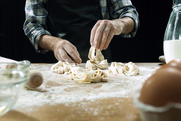 Cozinheiro profissional polvilha a massa com farinha