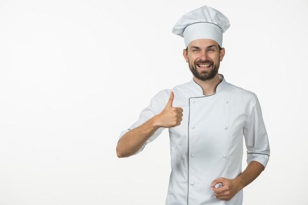 Cozinheiro profissional sorridente, mostrando o polegar para cima sinal contra o pano de fundo branco