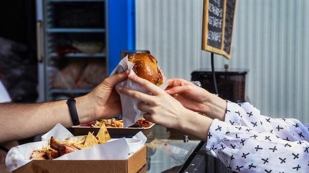 Cozinheiro terminando um hambúrguer e um cliente levando-o, food truck. comida de rua