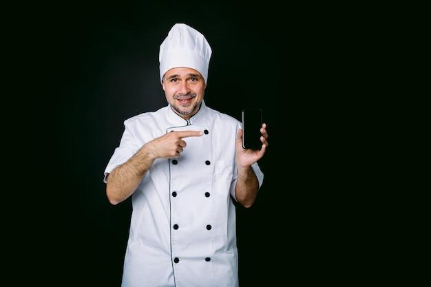 Cozinheiro vestido com chapéu branco e jaqueta apontando para seu telefone móvel em fundo preto. conceito de restaurante, comida e take-away.