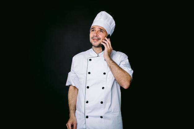 Cozinheiro vestido com chapéu branco e jaqueta falando ao telefone móvel em fundo preto. conceito de restaurante, comida e take-away.