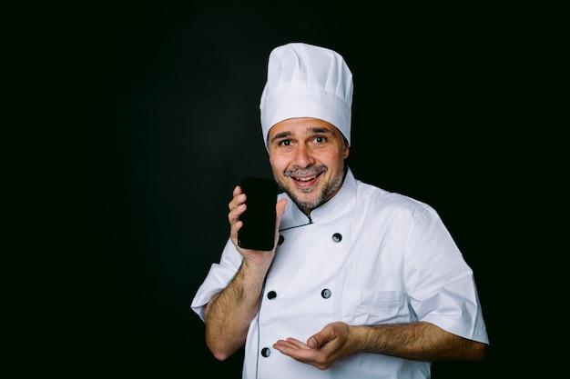 Cozinheiro vestido com chapéu branco e jaqueta mostrando seu celular em fundo preto. conceito de restaurante, comida e take-away.
