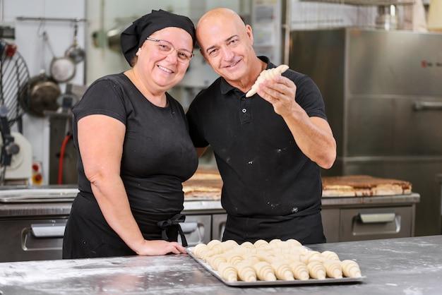 Cozinheiros chefe de pastelaria que fazem croissant deliciosos na cozinha da loja de pastelaria.