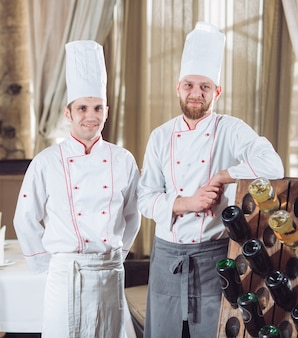Cozinheiros em um restaurante com garrafas de vinho