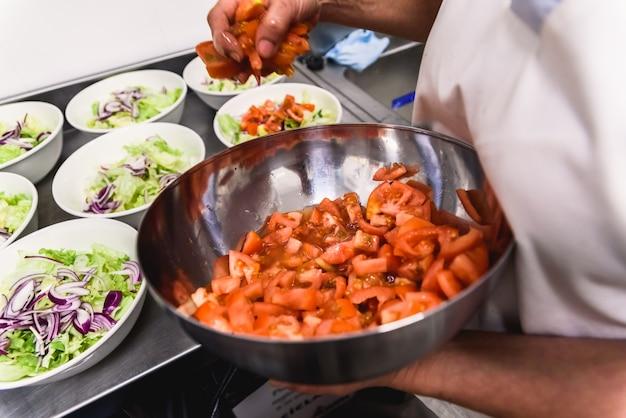 Cozinheiros preparando muitos pratos de salada com tomate e cebola alface dentro de sua cozinha.