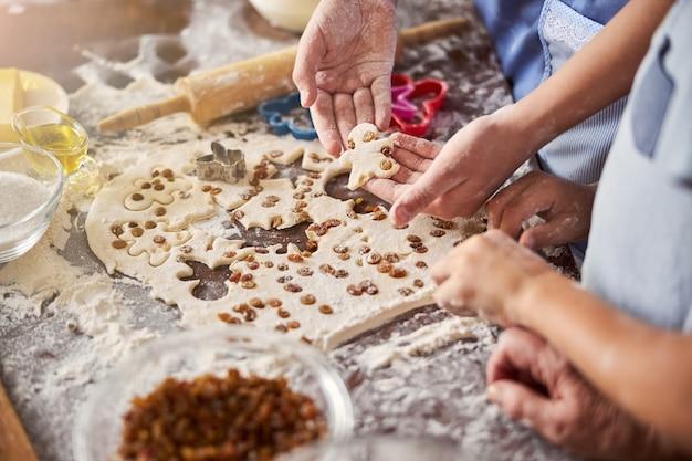Cozinheiros trabalhando à mesa cobertos de massa e suprimentos de comida