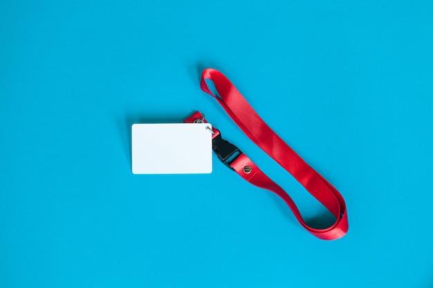 Crachá de plástico branco e cordão vermelho com simulação de espaço em branco isolado sobre fundo azul