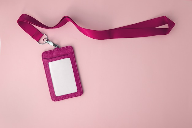 Crachá e cordão de couro em fundo rosa