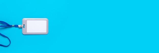 Crachá em branco com cordão em uma superfície azul clara