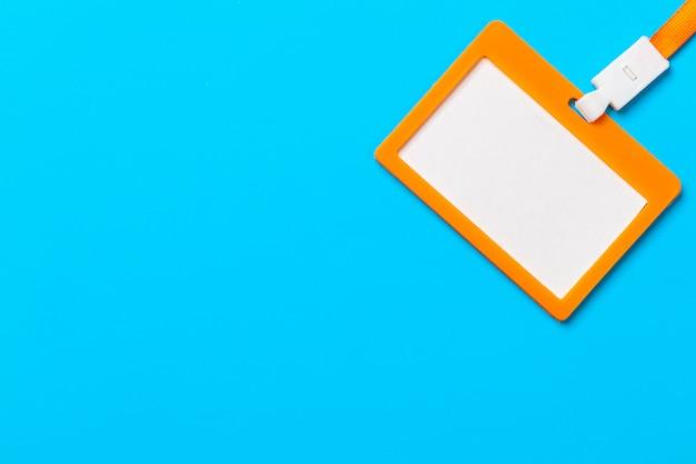 Crachá laranja com espaço de cópia no fundo de papel azul