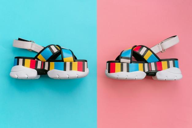 Cracóvia, polônia - 25 de abril de 2019: conjunto de sapatos femininos elegantes. sandálias das mulheres multicoloridas na moda de verão na cunha alta sobre fundo azul e rosa. calçado vogu e elegante para meninas modernas.
