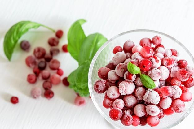 Cranberries congeladas em uma tigela de vidro com folhas de manjericão