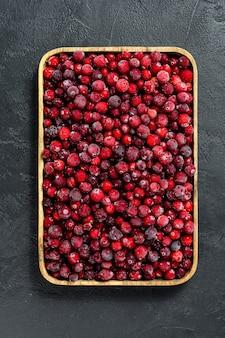 Cranberries congelados em uma tigela de madeira.