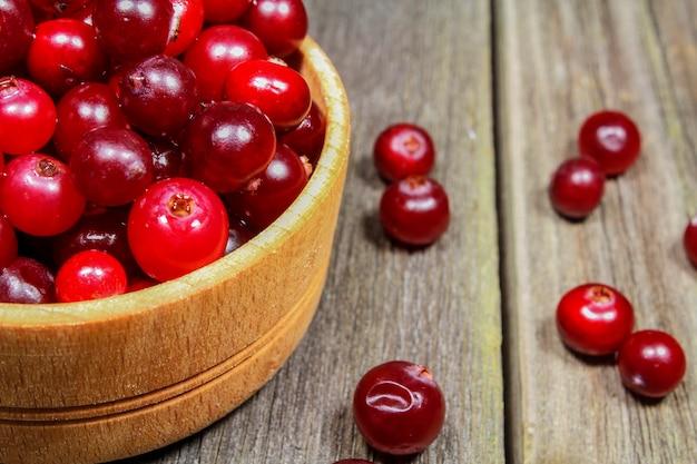 Cranberries em um copo de madeira sobre uma mesa de madeira