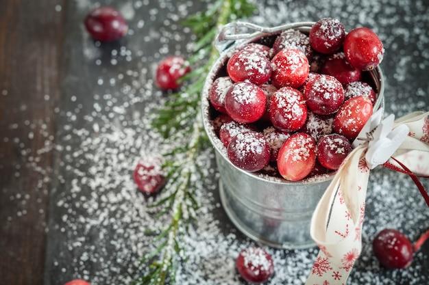 Cranberries em um pequeno balde de zinco decorado para o natal