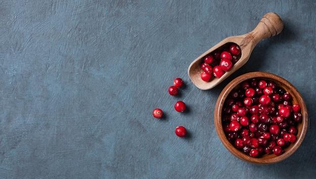 Cranberries frescas e doces em uma tigela de madeira sobre um fundo de madeira azul escuro. vista superior e espaço de cópia
