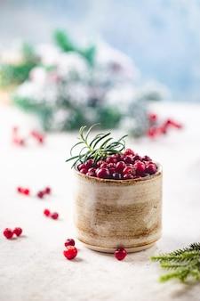 Cranberries frescas em uma tigela sobre fundo claro com decorações de inverno