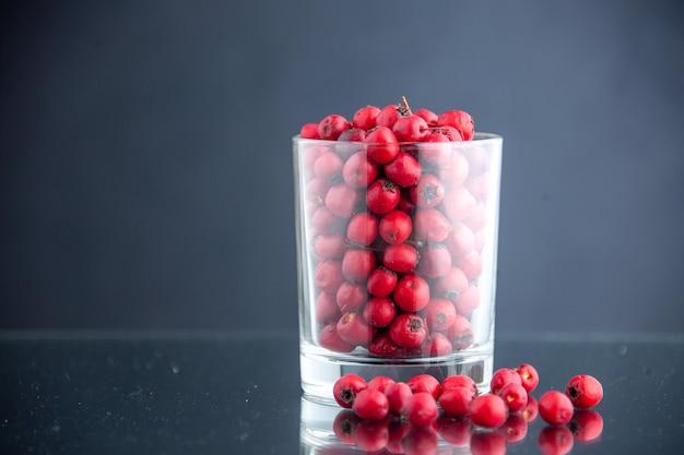 Cranberries vermelhos de vista frontal dentro de um vidro em um fundo escuro.