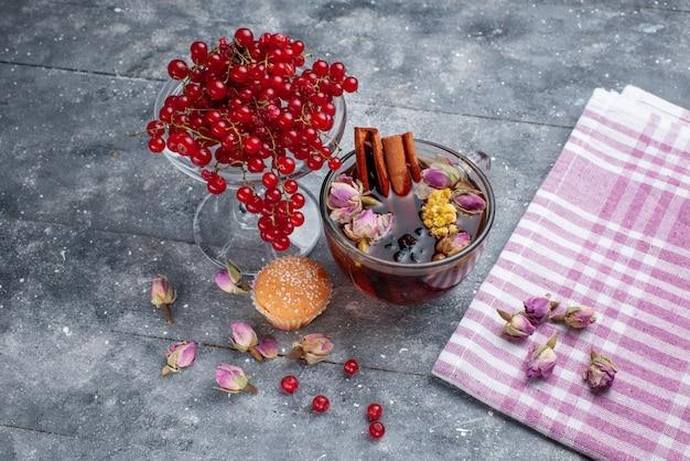 Cranberries vermelhos frescos com uma xícara de chá e canela na mesa de luz