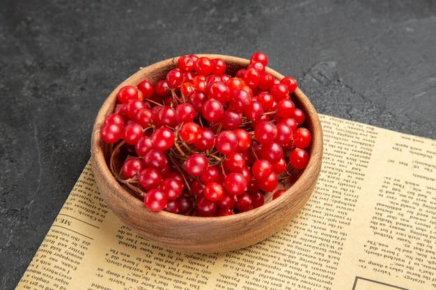 Cranberries vermelhos frescos em vista frontal em fundo escuro.