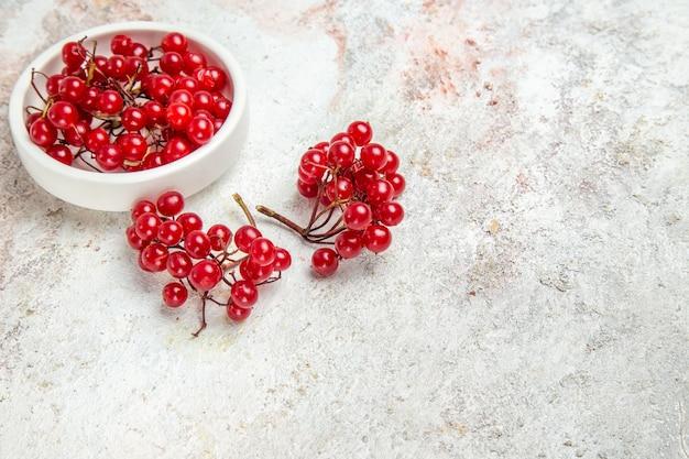 Cranberries vermelhos na mesa branca com frutas vermelhas frescas