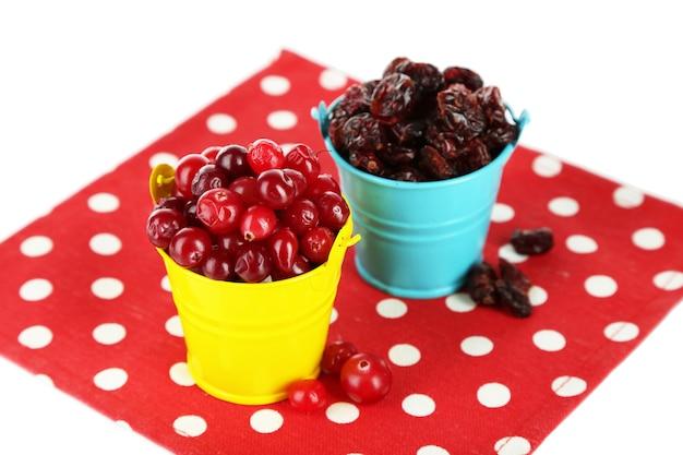 Cranberry fresco e seco em baldes coloridos, isolado no branco