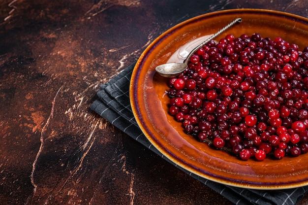 Cranberry vermelho maduro em um prato rústico. fundo escuro. vista do topo. copie o espaço.
