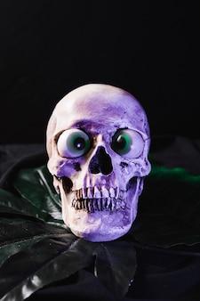 Crânio assustador com globos oculares fantasia iluminado pela luz roxa