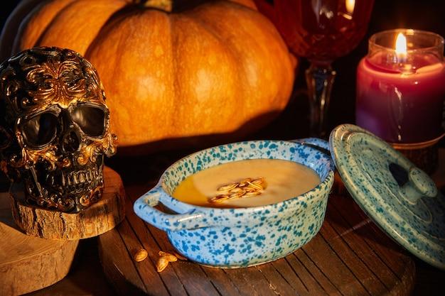 Crânio assustador de halloween com abóbora e sopa de creme na noite assustadora - cena de halloween.