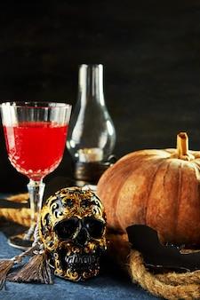 Crânio assustador de halloween com abóbora e vinho em uma noite assustadora.