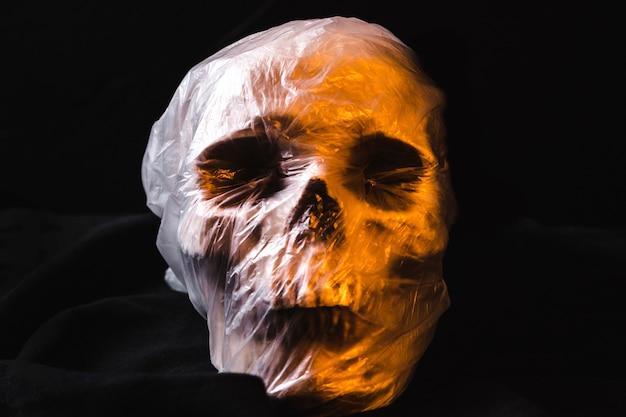 Crânio assustador em saco de plástico iluminado pela luz laranja